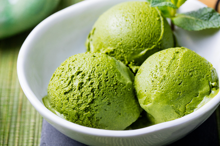 Green tea matcha ice cream scoop in white bowl on a wooden background Close up.