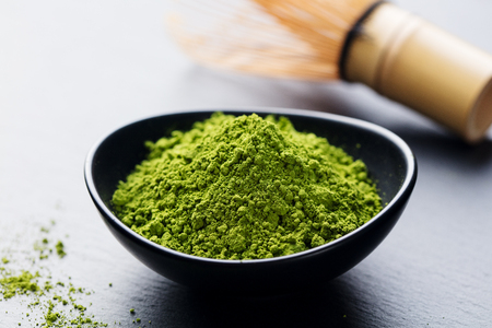 Matcha, green tea powder in black bowl with bamboo whisk on slate background. Copy space Stock Photo