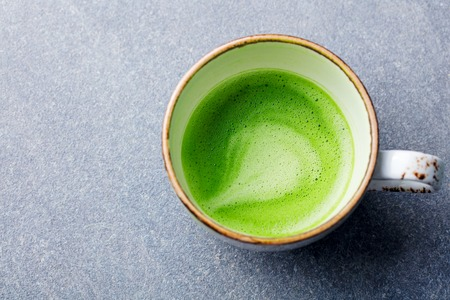 Matcha, green tea latte in a cup. Grey stone background. Top view. Close up