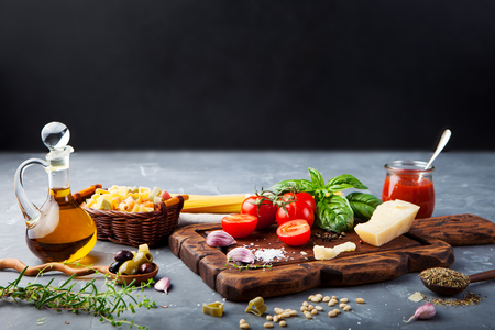 Italian food background with vine tomatoes, basil, spaghetti, olives, parmesan, olive oil, garlic Ingredients on stone table. Copy space. Stok Fotoğraf
