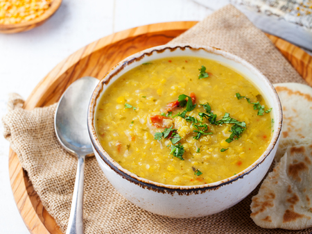 Lentil soup with pita bread in a ceramic white bowl on a wooden background. Close up