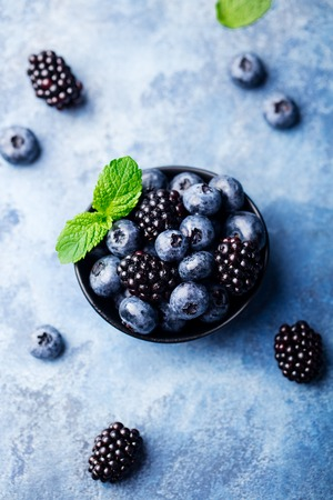 Blueberry and blackberry berries with mint leaves in black bowl on blue stone background. Top view