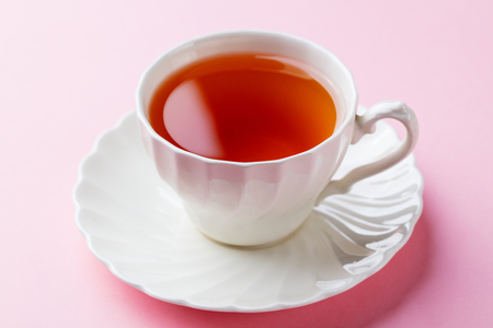 Tea in white cup on pink background. Close up