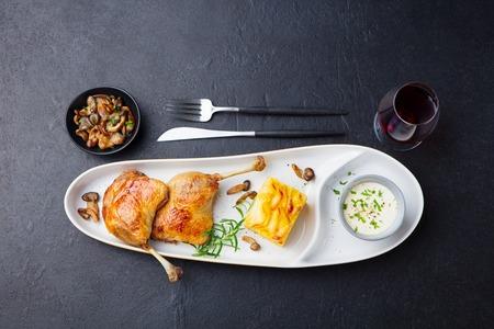 Duck legs confit, potato gratin and mushroom sauce