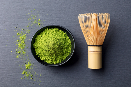Matcha, green tea powder in black bowl with bamboo whisk on slate background. Top view Reklamní fotografie