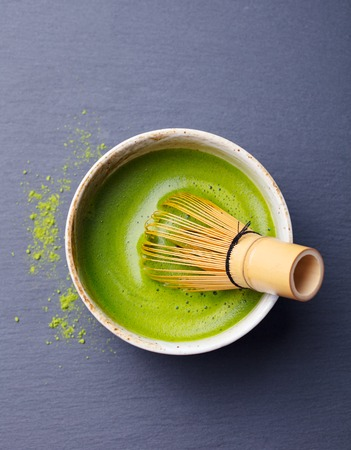 Matcha green tea cooking process in a bowl with bamboo whisk. Black slate background Stock Photo