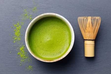 Matcha green tea cooking process in a bowl with bamboo whisk. Black slate background. Top view