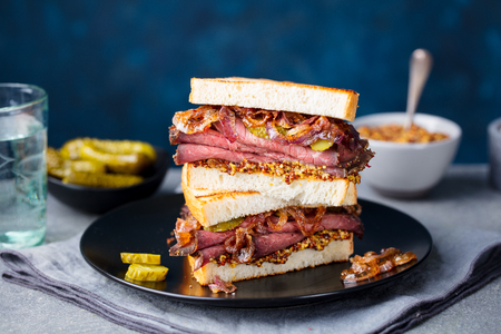 Roast beef sandwich on a plate with pickles. Copy space