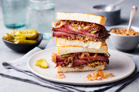 Roast beef sandwich on a plate with pickles