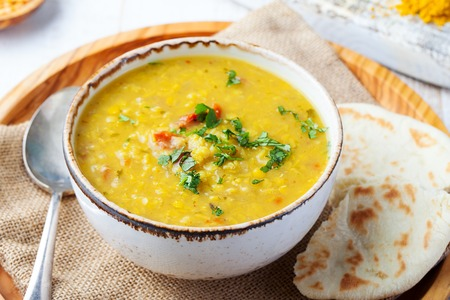 Lentil soup with pita bread in a ceramic white bowl on a wooden background. Close up Zdjęcie Seryjne - 96891919
