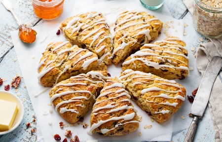 Scones with oats, cranberry and pecan nuts on wooden background. Top view. Banco de Imagens - 107428393