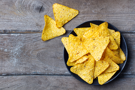 Nachos, corn chips on black plate. Wooden background. Top view. Copy space. Stock Photo