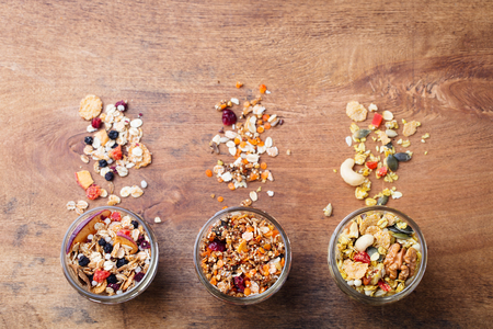 Assortment of granola, muesli in glass jars. Organic oats with fruits, berries, nuts. Top view. Copy space.
