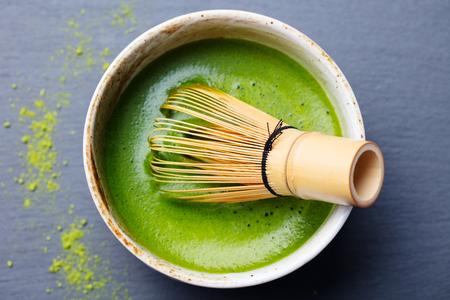 Matcha-Grüntee-Kochprozess in einer Schüssel mit Bambus-Schneebesen. Schwarzer Schieferhintergrund. Draufsicht. Standard-Bild