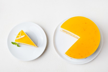 Passion fruit cake, mousse dessert on a white plate. Top view Stock Photo