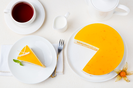 Passion fruit cake, mousse dessert on a white plate with cup of tea. Top view Stockfoto