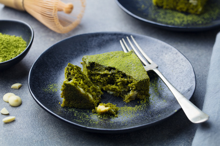 Matcha green tea cake, bars, brownie with white chocolate on a plate. Grey background 스톡 콘텐츠