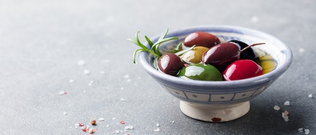 Olives assortment in bowl with oil. Copy space