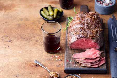 Roast beef on cutting board. Wooden background. Copy space