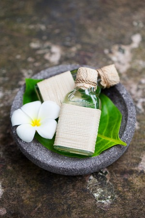Massage oil on grey wooden background with flowers. Top view. Stock Photo