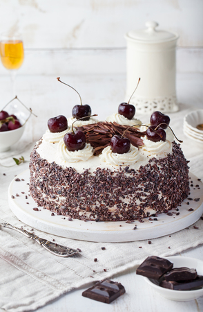 Torta della Foresta Nera, torta Schwarzwald, cioccolato fondente e dessert alla ciliegia su un tagliere di legno bianco Archivio Fotografico