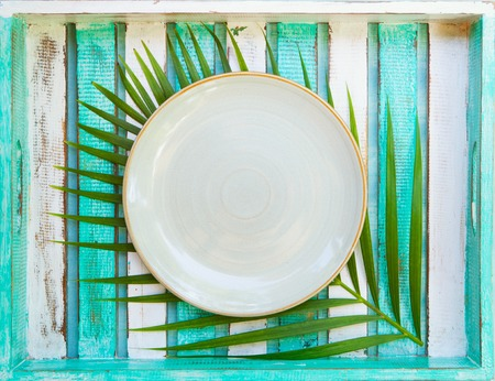 White plate with palm leaf on wooden background. Copy space. Top view.