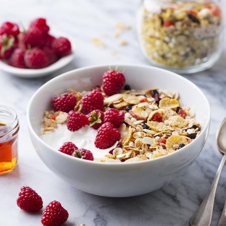 Healthy breakfast. Fresh granola, muesli with yogurt and berries on marble background