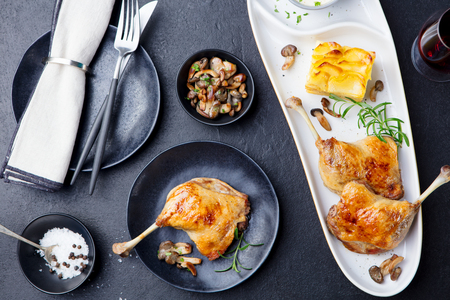 Duck legs confit with potato gratin and mushroom sauce. Restaurant serving. Top view. Stok Fotoğraf