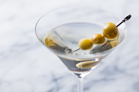 Martini cocktail with green olives on marble board. Close up. Stock Photo