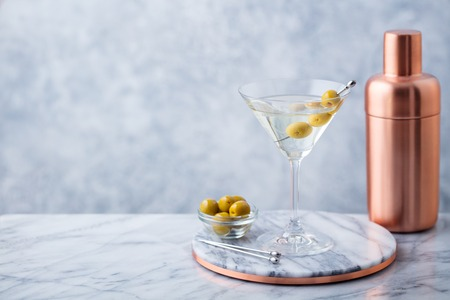 Martini cocktail with olives and bar shaker on marble table background. Copy space. Stockfoto