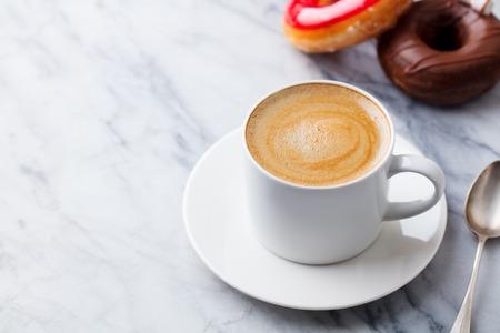 Taza de café con donas en el fondo de la mesa de mármol. Copie el espacio. Foto de archivo