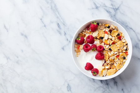 Healthy breakfast. Fresh granola, muesli with yogurt and berries on marble background. Top view. Copy space. Stok Fotoğraf