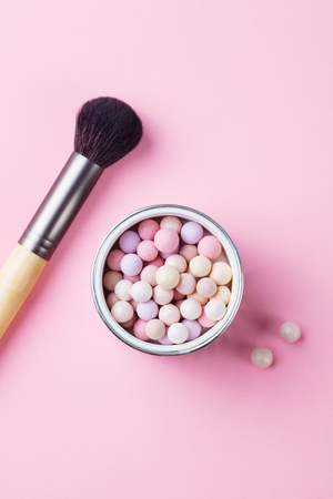 Pearl make up powder on pink pastel background. Top view.