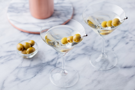 Martini cocktail with olives and bar shaker on marble table background. Copy space.