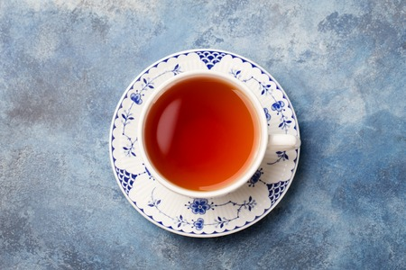 Cup of tea on a blue stone background. Copy space. Top view.