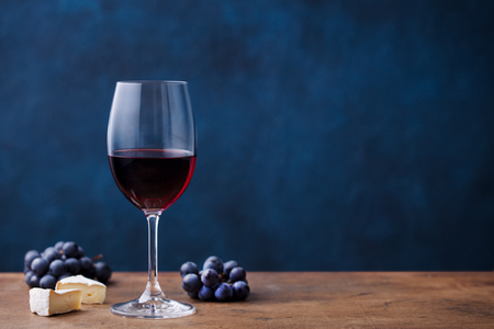 Glass of red wine with fresh grape and cheese on wooden table. Blue background. Copy space Stock Photo