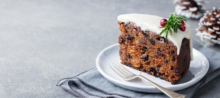 Christmas fruit cake, pudding on white plate. Copy space