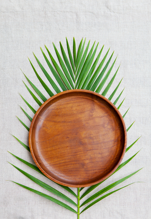 Wooden plate with palm leaf on natural linen textile background. Copy space. Top view
