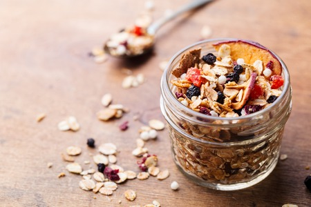 Granola, muesli in glass jar. Healthy breakfast. Organic oats with apples berries and nuts. Copy space. Stock Photo