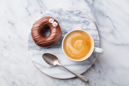Coffee in a white cup with chcolate donut on marble board. Top view