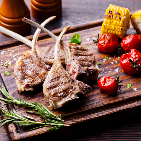 Lamb ribs grilled on cutting board with roasted vegetables. Close up Stok Fotoğraf