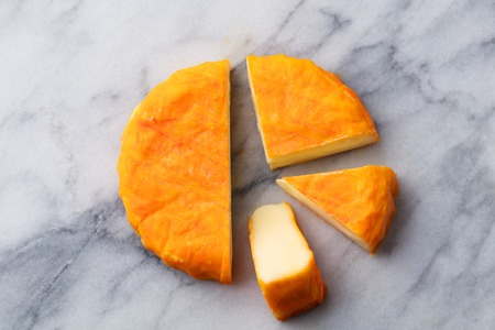 Cheese with washed orange rind. French or German. Marble table background. Top view