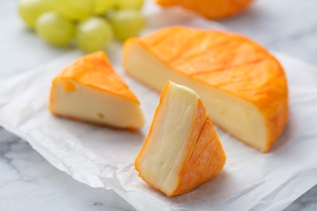 Cheese with washed orange rind. French or German. Marble table background. Close up