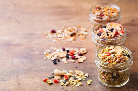 Assortment of granola, muesli in glass jars. Healthy breakfast. Organic oats with apples, berries and nuts. Copy space