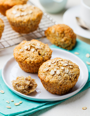 Healthy vegan oat muffins, apple and banana cakes with sour cream on a white plate. Blue background