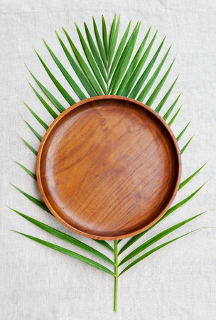 Wooden plate with palm leaf on natural linen textile background. Copy space. Top view. Stock Photo