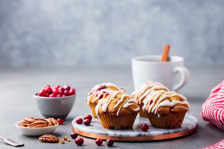 Muffins mit Preiselbeer- und Pekannüssen auf Marmorbrett. Grauer Steinhintergrund. Speicherplatz kopieren
