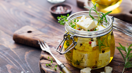 Feta cheese marinated in olive oil with fresh herbs in glass jar. Wooden background. Copy space