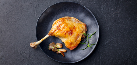 Duck leg confit with mushroom sauce on black plate. Slate background. Top view Stok Fotoğraf - 107500595