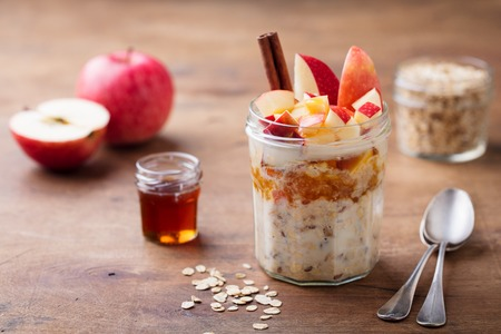 Overnight oats, bircher muesli with apple, cinnamon and honey. Wooden background 스톡 콘텐츠